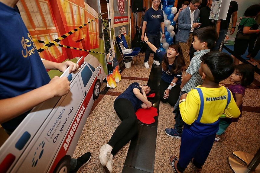"""Children learning about giving first aid in an """"emergency"""" situation at Gleneagles Hospital's 60th Anniversary Carnival. The hospital has pledged to raise funds to help 60 beneficiaries of The Straits Times School Pocket Money Fund with $60 a month f"""