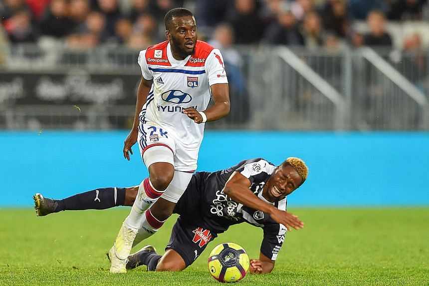 France midfielder Tanguy Ndombele, beating Bordeaux's Francois Kamano while playing for Lyon in a French Ligue 1 game in April, is Tottenham's No. 1 transfer target. PHOTO: AGENCE FRANCE-PRESSE