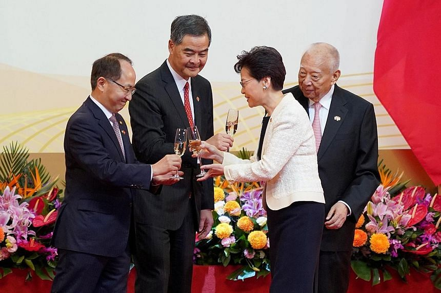 Hong Kong Chief Executive Carrie Lam raising a toast with (from left) Mr Wang Zhimin, director of China's Liaison Office in Hong Kong, and her predecessors Leung Chun Ying and Tung Chee Hwa, at the Convention and Exhibition Centre in Wanchai yesterda