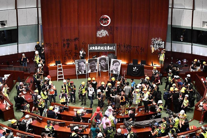 Protesters and members of the media inside the vandalised legislative chamber of the LegCo building yesterday evening. ST PHOTO: LIM YAOHUI