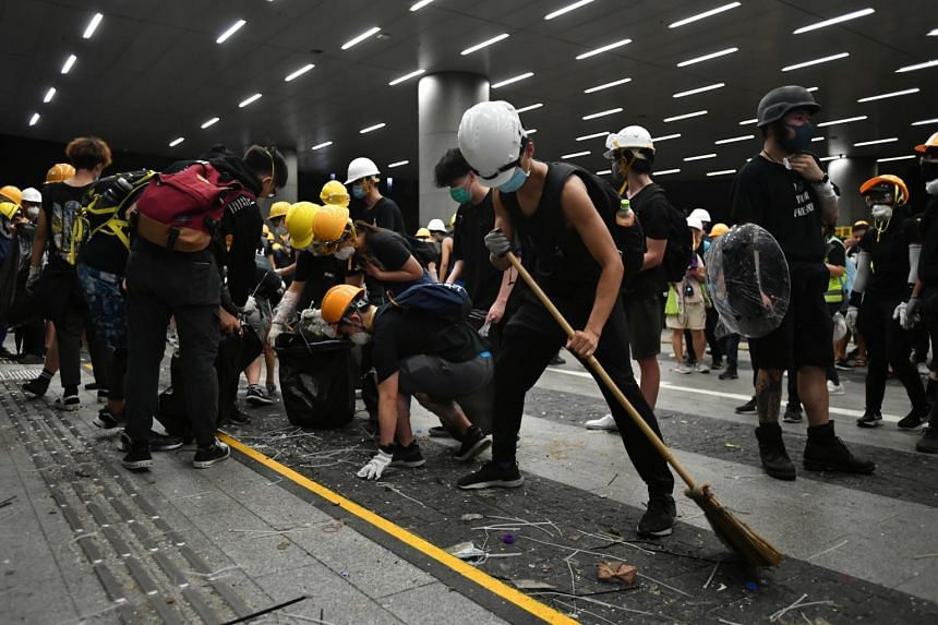 Protesters cleaning up trash at the entrance of the Legislative Council complex on July 1, 2019.