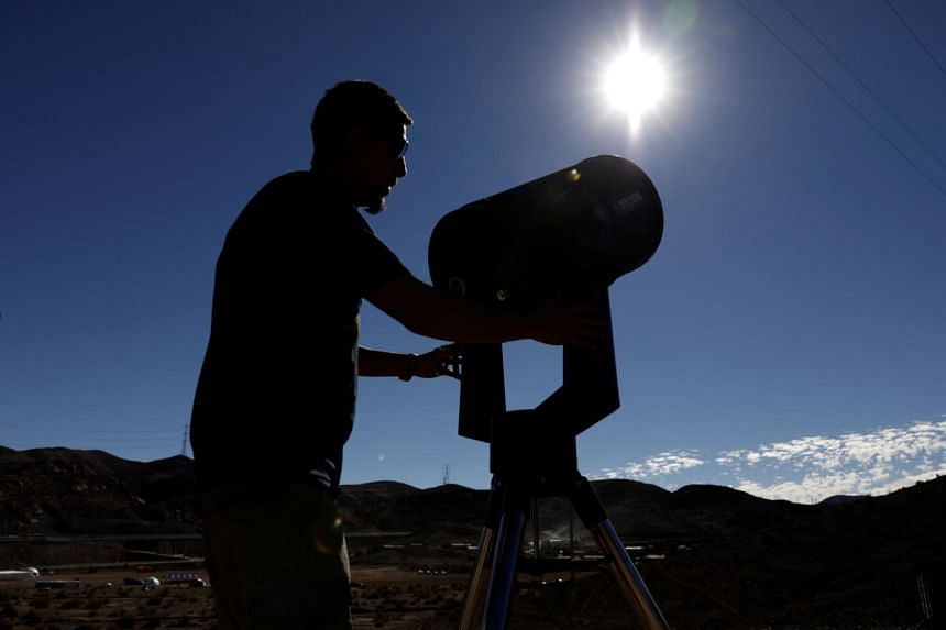 A man prepares to observe the sun with a telescope in Incahuasi, Chile, on July 1, 2019.