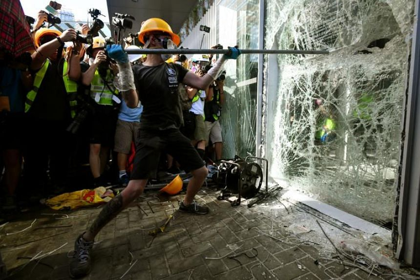Protesters arm themselves with shields and umbrellas from pepper spray used by the police as they try to break a window of the Legislative Council building in Hong Kong on July 1, 2019.