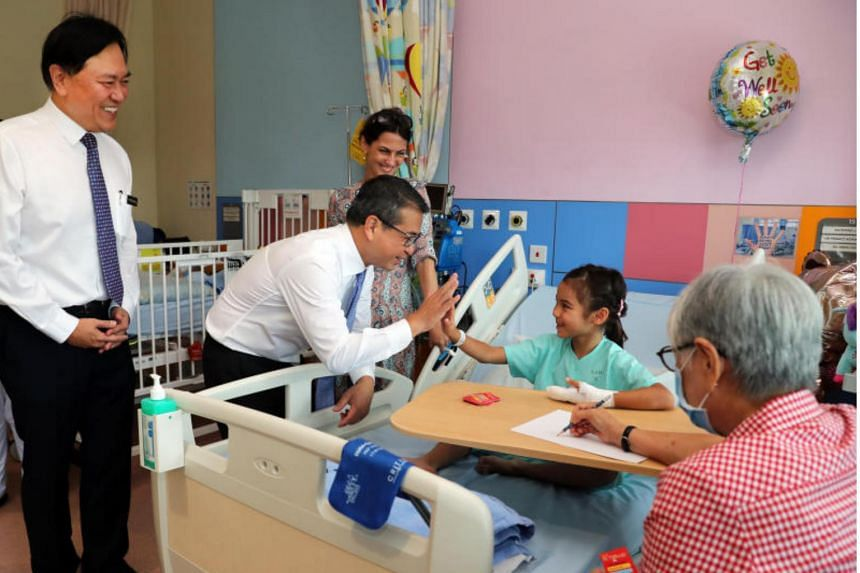 (From left) Professor Alex Sia, chief executive officer of  KK Women's and Children's Hospital; and Mr Edwin Tong, Senior Minister of State for Health, interacting with patient Katerina Loh as Katerina's mum, Galina Ivanovo, looks on.