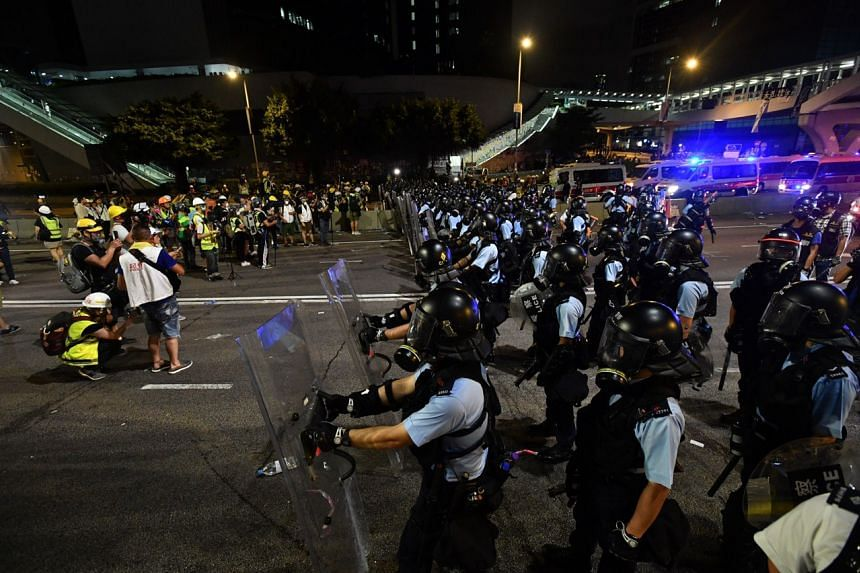 Riot police clash with protesters as they arrive to disperse protesters from the Legislative Council Building in Hong Kong on July 1, 2019.