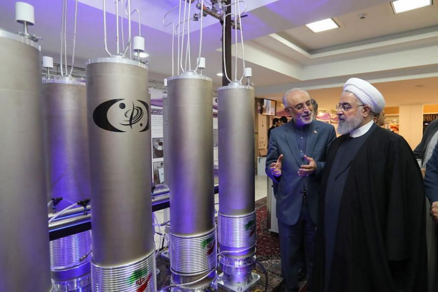 Iranian President Hassan Rouhani and the head of Iran nuclear technology organisation Ali Akbar Salehi inspecting nuclear technology in Teheran on April 9, 2019.