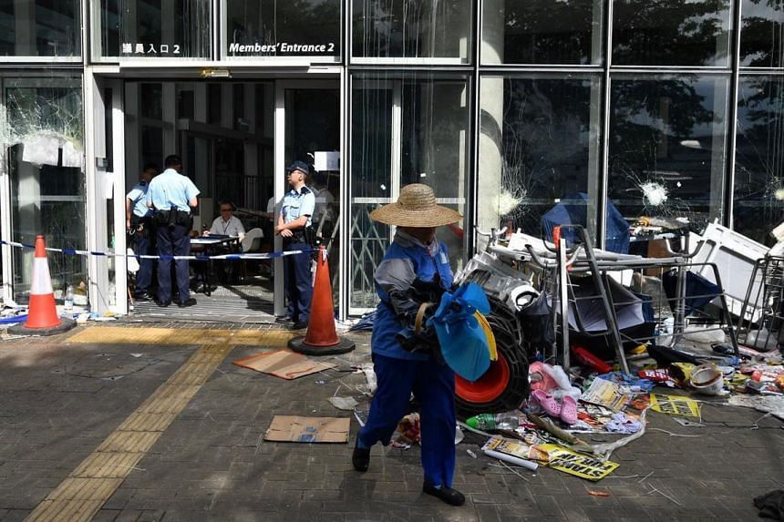 A working cleaning up outside the Legislative Council building after it was occupied by protesters, on July 2, 2019.