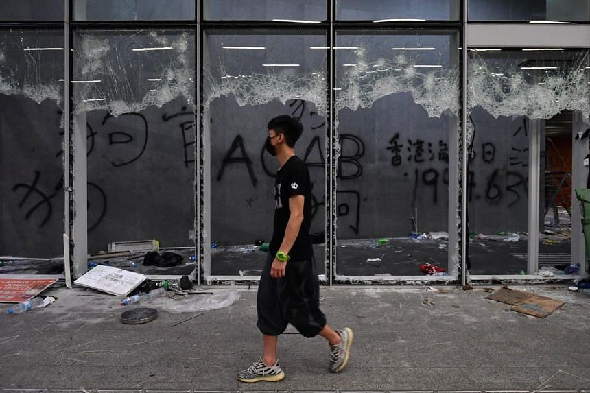 A protester walks past graffiti after the Legislative Council building was stormed by protesters on July 1, 2019.
