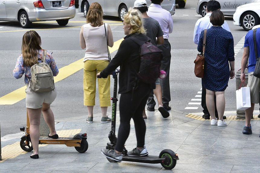 Women riding e-scooters on the pavement.