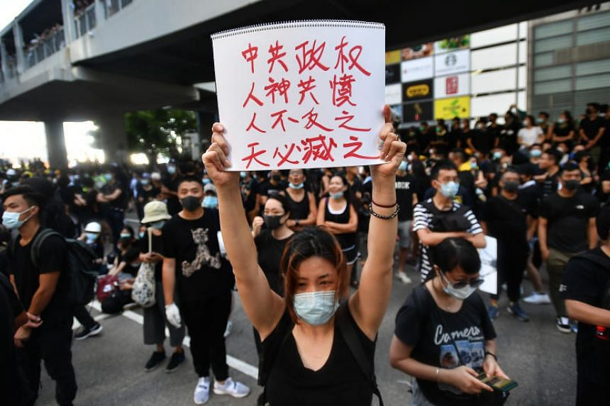A protester holds up a protest placard outside the Legislative Council Complex, in Hong Kong, on July 1, 2019.