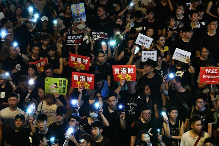 Protesters switch on their phones' flashlights during the annual pro-democracy march in Hong Kong on July 1, 2019, the anniversary of its handover to Beijing in 1997.