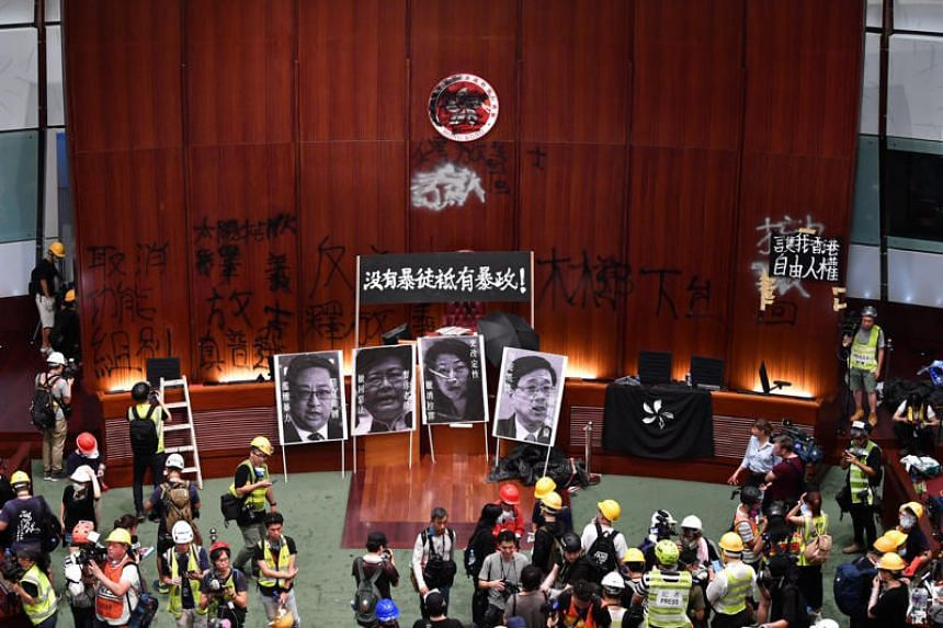Protesters vandalised the parliament chambers and displayed posters of politicians including Hong Kong Chief Executive Carrie Lam (second from left) in the legislature building on July 1, 2019.
