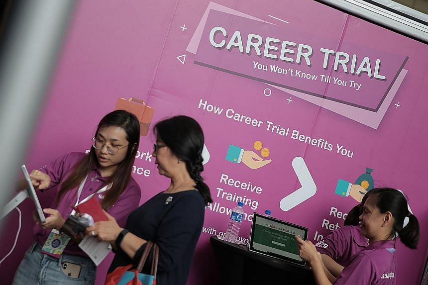 Mr Dicky Dzulkarnaen found a full-time job as a guest services officer at Park Regis Singapore through the Career Trial scheme. Workforce Singapore staff assisting a job-seeker at the Career Trial booth at the Adapt and Grow Career Fair at HDB Hub ye