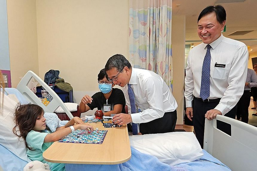 Senior Minister of State for Health Edwin Tong with Svea Nadia Hertzman, eight, at the children's ward of KK Women's and Children's Hospital (KKH) yesterday. He was accompanied by KKH chief executive Alex Sia.