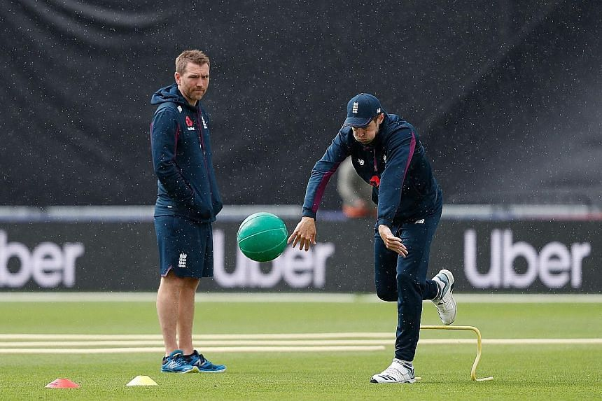 England all-rounder Chris Woakes throwing a medicine ball as a support staff member looks on during training last month at the Cricket World Cup. The top-ranked hosts are gunning for their first title.