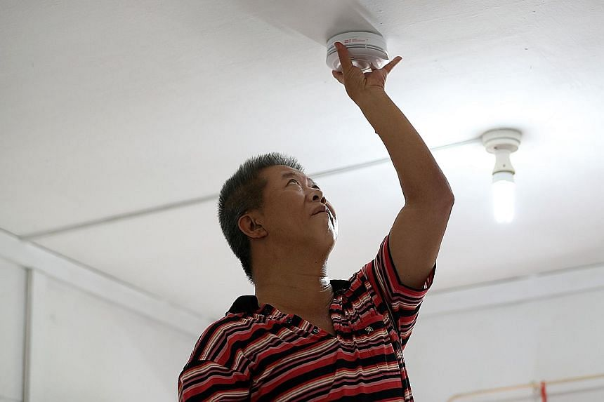 Above: Mr Gilroy Chan, 56, had the Home Fire Alarm Device installed in his rental flat as he believes in taking precautions. Right: Madam Marina Mohd Ali, 32, believes that the Home Fire Alarm Device will help ensure the safety of her children when t