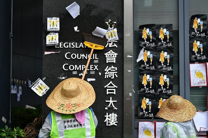 Cleaners scraping off posters put up by protesters at the Legislative Council Complex in Hong Kong yesterday as the city cleaned up after the overnight violence. Calm returned to the city yesterday, but the LegCo building was sealed off by police. Al
