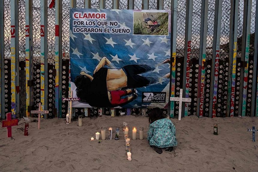 A girl lighting candles in front of a poster of Mr Oscar Alberto Martinez Ramirez and his daughter, Valeria, who both drowned.