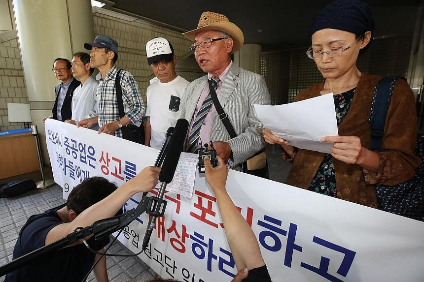 Japanese Prime Minister Shinzo Abe and South Korean President Moon Jae-in had some awkward moments at the G-20 summit amid souring ties. PHOTO: REUTERS Family members and representatives responding to reporters at the Appellate Court in Seoul on June