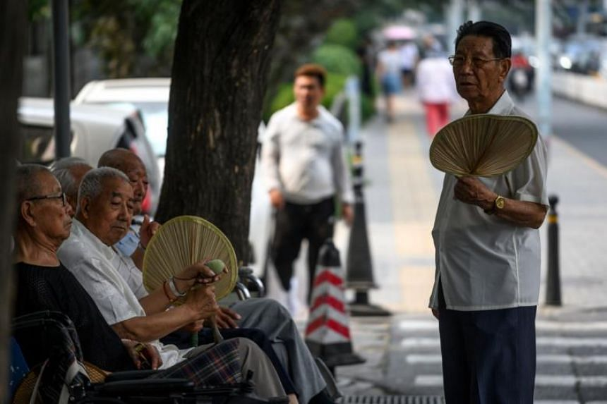 Elderly people use fans to cool themselves off, in Beijing on June 26, 2019.