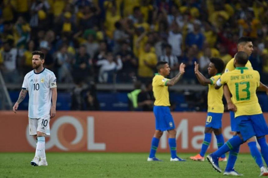 Argentina's Lionel Messi leaves the field as Brazil's players celebrate at the end of their Copa America football tournament semi-final match at the Mineirao Stadium in Belo Horizonte, Brazil, on July 2, 2019.