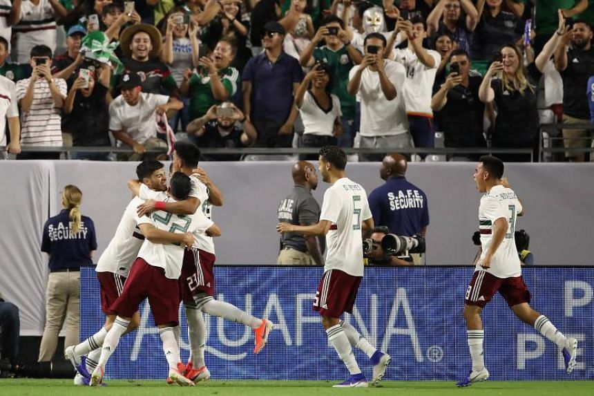 Mexican players celebrate after scoring a penalty against Haiti during overtime of the Concacaf Gold Cup semi-final match at State Farm Stadium on July 2, 2019.