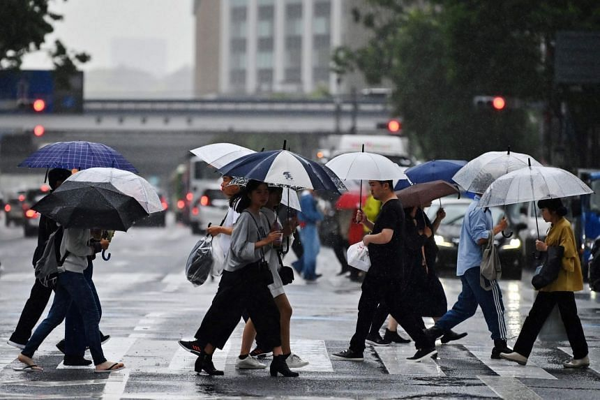 People cross a street during a rainy afternoon in Tokyo, Japan, on May 21, 2019.
