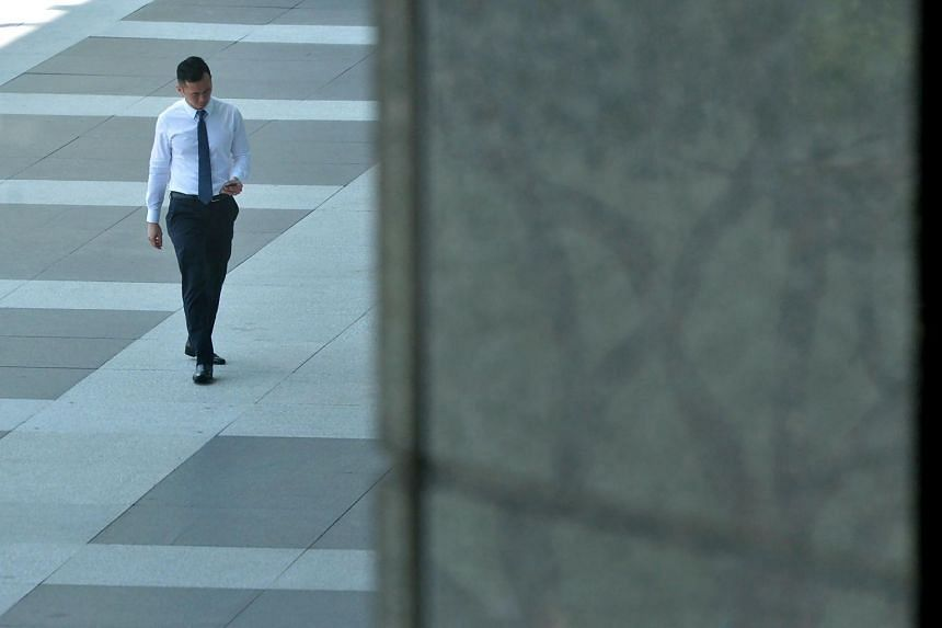 An office worker looking at his phone at Raffles Place.