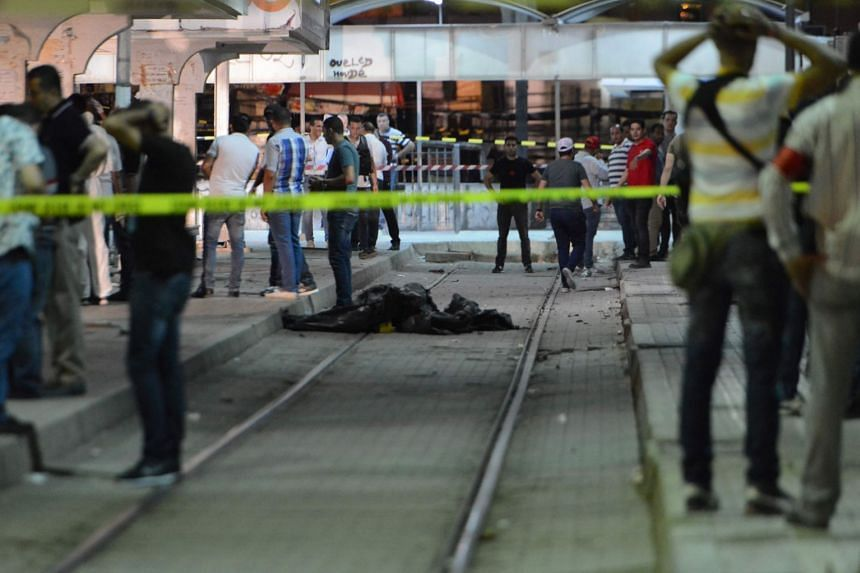 Onlookers gather at the scene outside a metro station where a man reportedly wearing an explosive belt blew himself up.