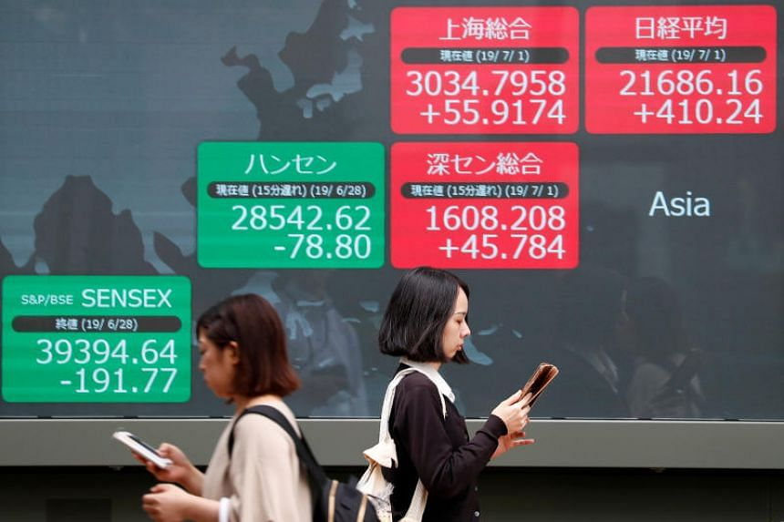 An electric screen showing Asian markets indices outside a brokerage in Tokyo on July 1, 2019.