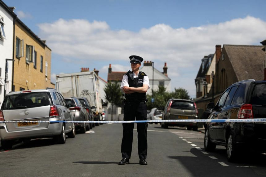 A police officer stands at the cordon on the street where a heavily pregnant woman was stabbed to death in the Thornton Heath area of London on June 30, 2019.