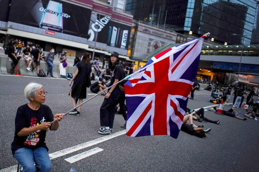 Ms Alexandra Wong, 63, holds up a Union Jack flag during a demonstration demanding Hong Kong's leaders step down and withdraw an extradition Bill, in Hong Kong on June 17, 2019.