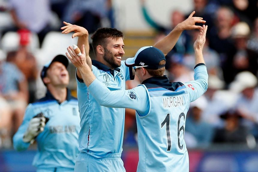 England's Mark Wood celebrates with Eoin Morgan after taking the wicket of New Zealand's James Neesham.