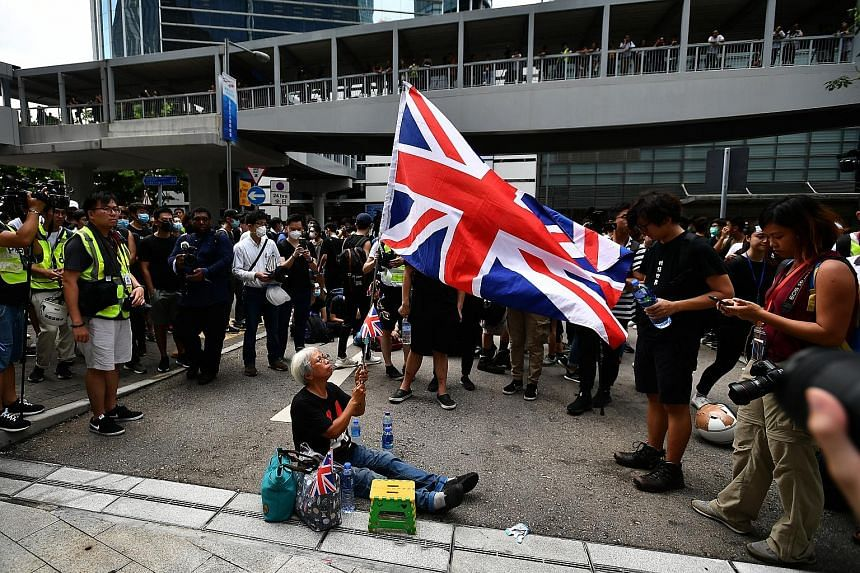 Ms Alexandra Wong has been on the front lines of protests. She is seen here waving the Union Jack at the entrance of the LegCo building on June 21.