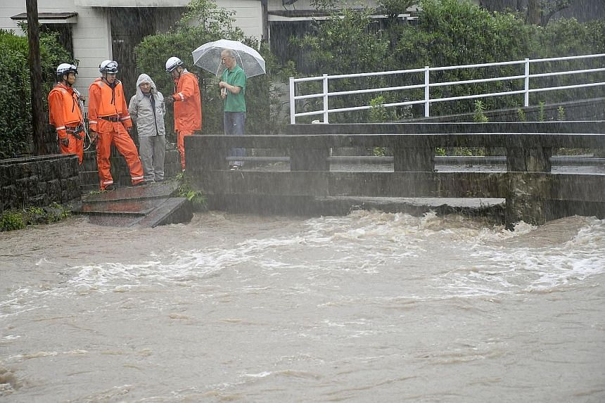 The Wada River in Kagoshima, south-western Japan, threatening to overflow due to heavy rain yesterday. Heavy rainfall has brought waist-deep floods to south-west Japan and caused at least 30 deaths in India's financial capital Mumbai.