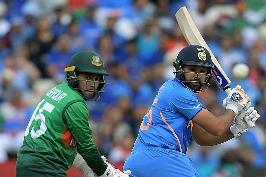 India's Rohit Sharma and Bangladesh wicketkeeper Mushfiqur Rahim watching a shot during their match at Edgbaston in Birmingham on Tuesday. Sharma scored 104 in India's 28-run victory. PHOTO: AGENCE FRANCE-PRESSE