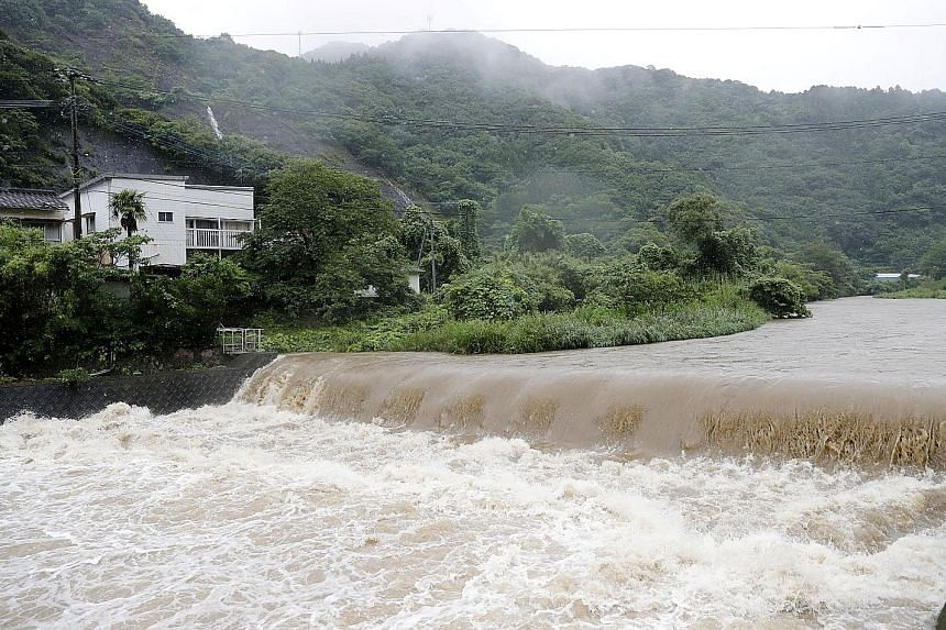 The Futami River swelling because of heavy rain in Yatsushiro, Kumamoto prefecture, in south-western Japan, yesterday. Many areas have seen more rain in a single day than in a typical month of July.