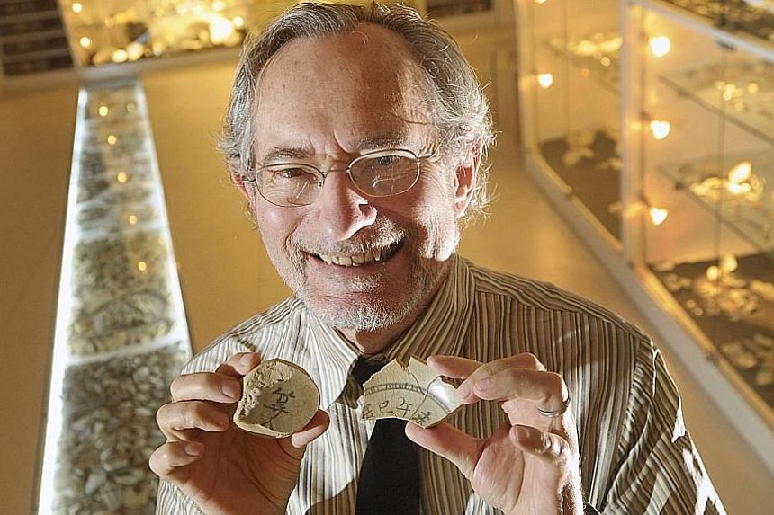 Professor John Miksic holding up fragments of a rare 14th century Chinese ceramic compass he unearthed on Fort Canning Hill. The compass could have been used for fengshui divination. Other items found were a gold armlet (above) and a bust of a man po
