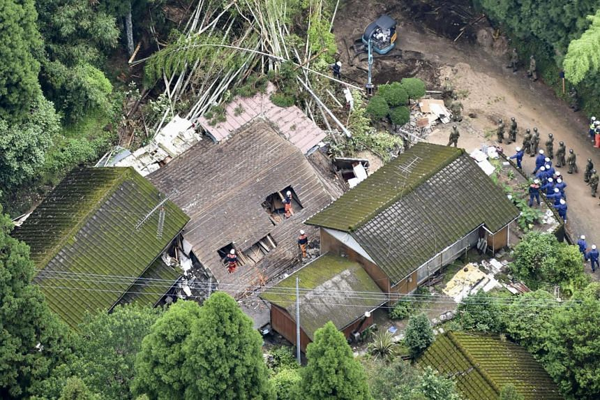 Rescue workers searching for a missing resident at a collapsed house following a landslide caused by heavy rain in Soo, Kagoshima prefecture, on July 4, 2019.