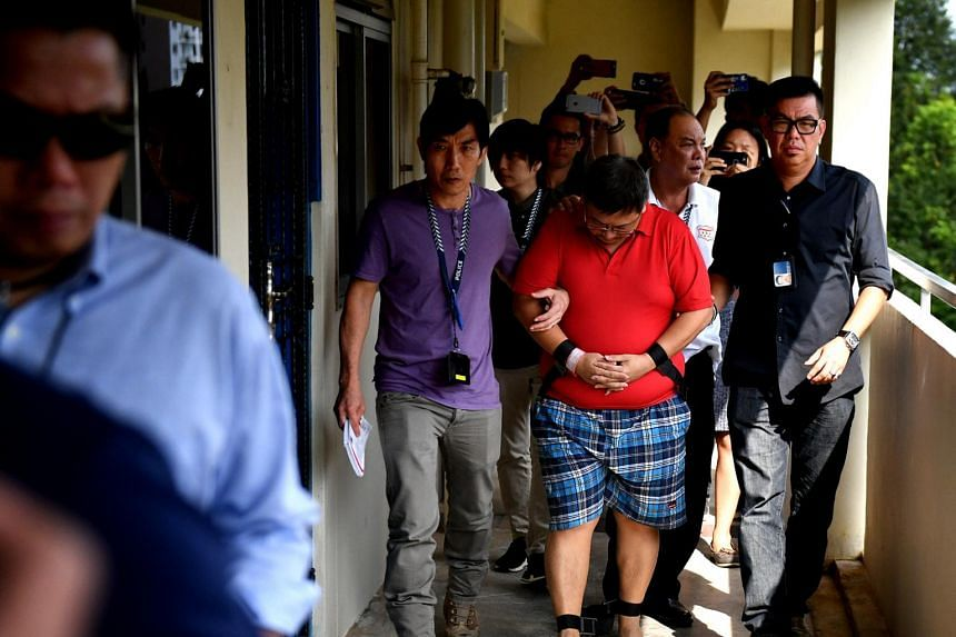 Woodlands double-murder suspect Teo Ghim Heng (in red) being escorted by police to his flat at Block 619 Woodlands Drive 52 on Feb 10, 2017.