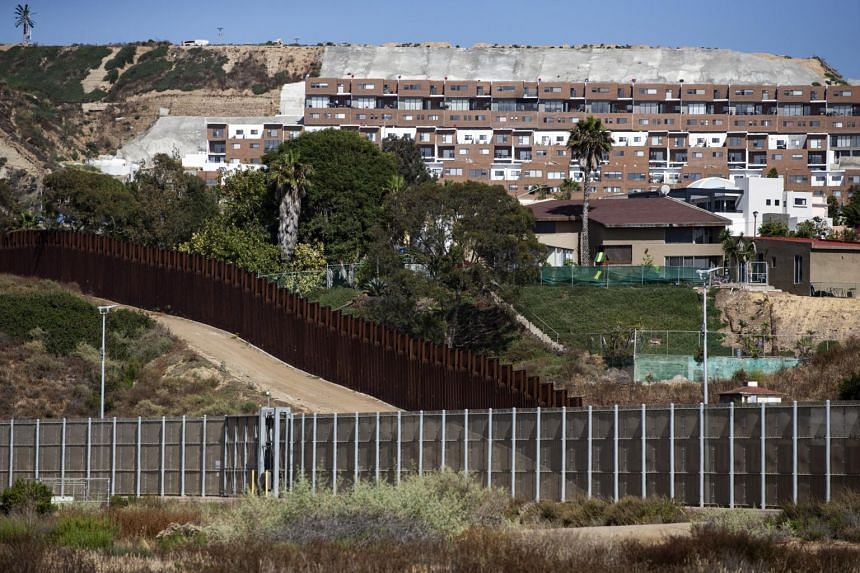 Buildings in Tijuana overlook the wall demarcating the border between the US and Mexico in San Diego, California, on July 3, 2019.