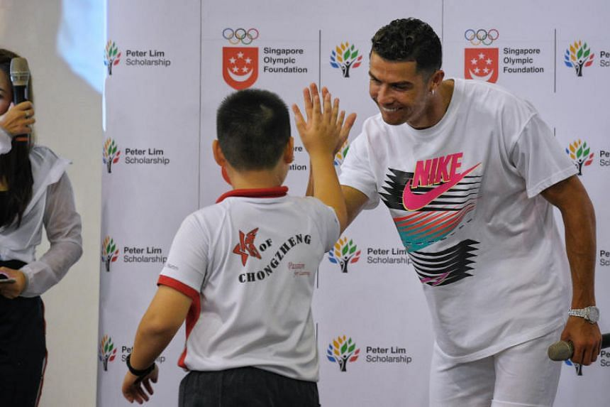 Cristiano Ronaldo greets a Chongzheng Primary School pupil during a visit to Yumin Primary School on July 4, 2019.