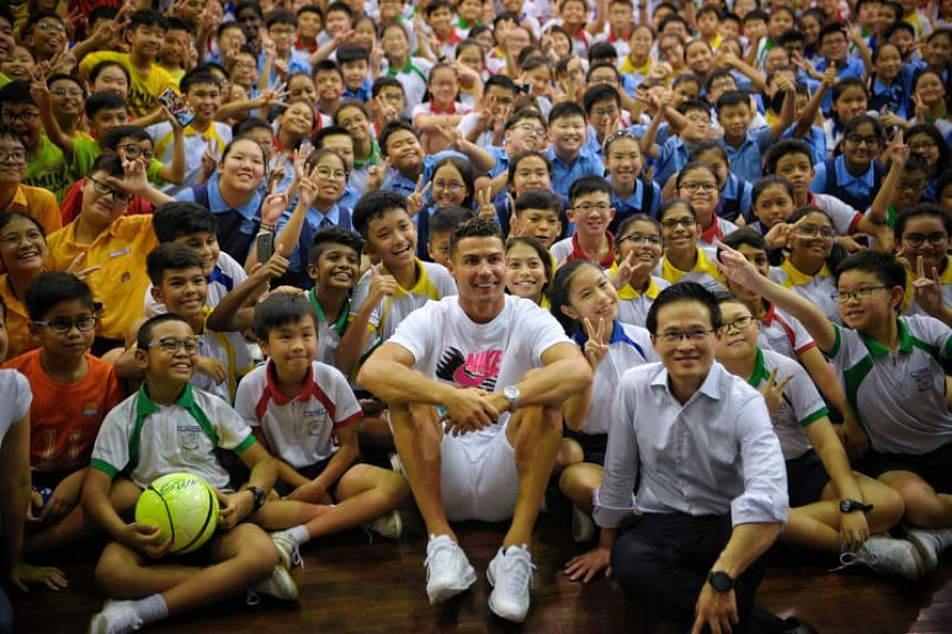 Cristiano Ronaldo and Tampines GRC MP Desmond Choo with pupils from Yumin Primary School and Chongzheng Primary School on July 4, 2019.