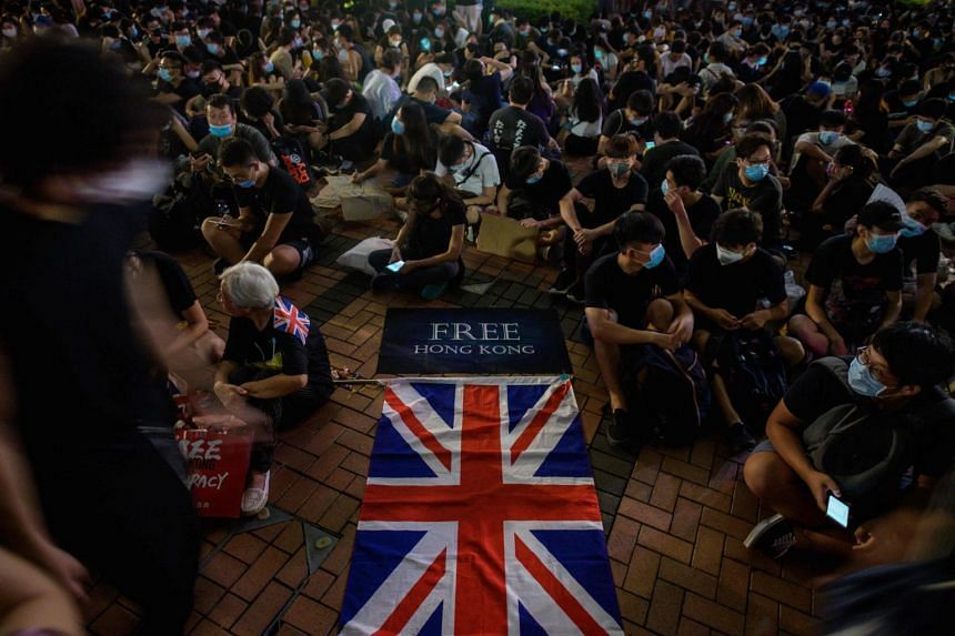 A British Union Jack flag is displayed as protesters gather along a fenced-off Victoria Harbour pier in Hong Kong, on June 28, 2019.