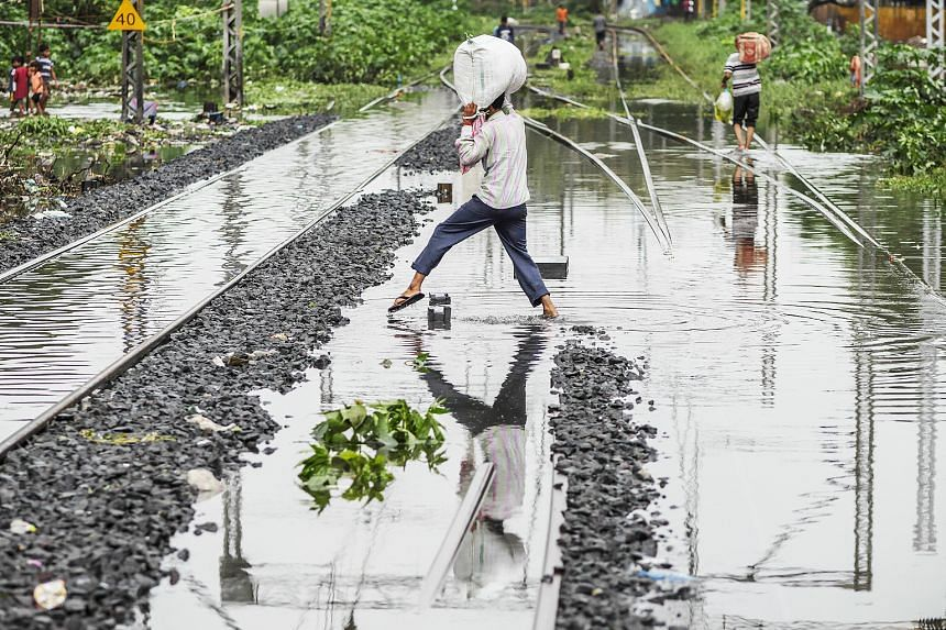 People making their way across submerged rail tracks in Mumbai. Over 375.2mm of rain fell on the Indian city in the 24 hours ending at 8.30am local time on Tuesday, shutting down schools and disrupting transport. It was Mumbai's second highest rainfa