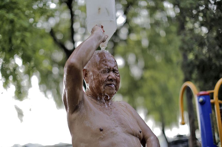 An elderly man splashing himself after a swim in the Houhai lake in Beijing. Residents like him swim in the lake to cool down to avoid heatstroke as temperatures in the Chinese capital soar.