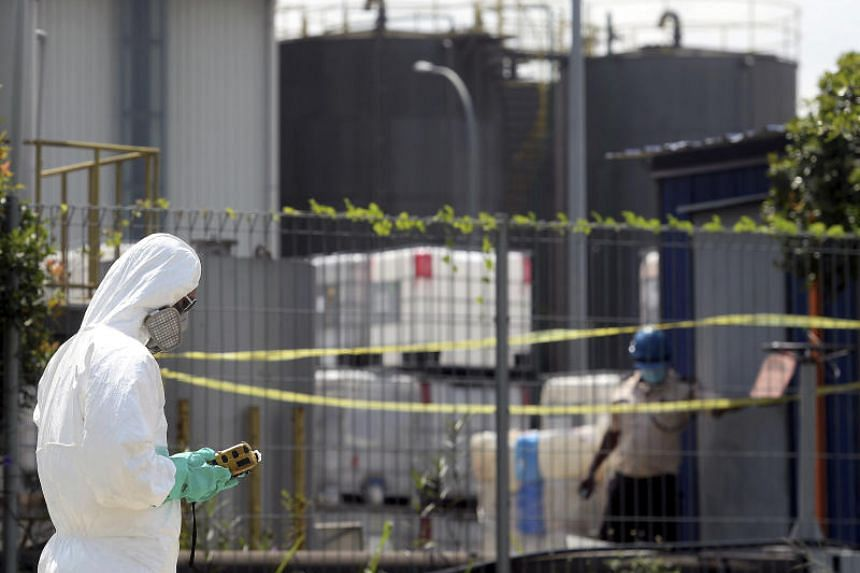 Malaysia's Department of Environment officials conducting air quality reading checks at factories near the Pasir Gudang area in Johor on June 25, 2019.
