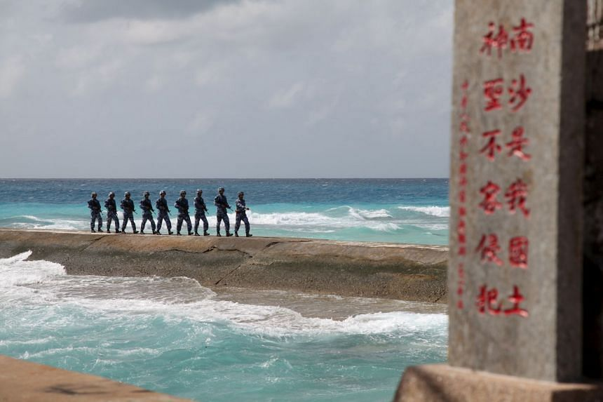 """People's Liberation Army soldiers patrol near a sign in the Spratly Islands, known in China as the Nansha Islands, in 2016. The sign reads """"Nansha is our national land, sacred and inviolable."""""""
