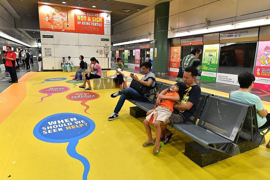 Advertisements at Sengkang MRT station promoting fertility health checks to couples. A new poll of 1,000 respondents found more than half knew someone having difficulty trying for a first or second child, with nearly 70 per cent wrongly thinking that