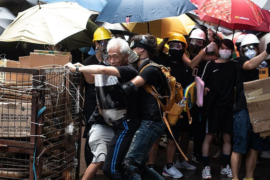 Hong Kong pro-democracy lawmaker Leung Yiu-chung (left) being held back by protesters as he tries to stop them from trying to break a window at the government headquarters on Monday, the 22nd anniversary of the city's handover from Britain to China.